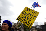 An anti-Brexit campaigner holds a banner near Parliament in London, Tuesday, Oct. 8, 2019. The British government said Tuesday that the chances of a Brexit deal with the European Union were fading fast, as the two sides remained unwilling to shift from their entrenched positions. (AP Photo/Kirsty Wigglesworth)