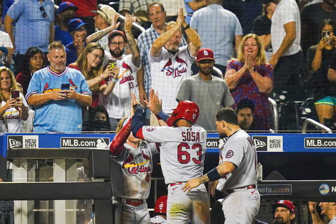 Fans watch as St. Louis Cardinals' Edmundo Sosa (63) celebrates with teammates after scoring on a two-run single by Andrew Knizner during the 11th inning of the team's baseball game against the New York Mets on Tuesday, Sept. 14, 2021, in New York. (AP Photo/Frank Franklin II)