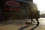 People walk their dog outside of Wrigley Field on opening day for the Chicago Cubs on Thursday, April 1, 2021, in Chicago. The Cubs play the Pittsburgh Pirates. The U.S. moved closer Thursday, April 1, toward vaccinating 100 million Americans in a race against an uptick in COVID-19 cases that is fueling fears of another nationwide surge just as the major league baseball season starts and thousands of fans return to stadiums. (AP Photo/Shafkat Anowar)