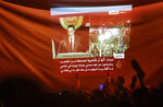 FILE - In this Feb. 10, 2011 file photo, protesters wave their shoes in the air in contempt as they watch a projection of the televised speech of Egyptian President Hosni Mubarak, in Cairo, Egypt. The 2011 uprising led to the quick ouster of autocrat Mubarak. A decade later, thousands are estimated to have fled abroad to escape a state, headed by President Abdel Fattah el-Sissi, that is even more oppressive.  (AP Photo/Ben Curtis, File)