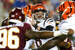 Cincinnati Bengals quarterback Brandon Allen (8) looks to pass under pressure from Washington Football Team defensive end James Smith-Williams (96) during the first half of a preseason NFL football game Friday, Aug. 20, 2021, in Landover, Md. (AP Photo/Susan Walsh)