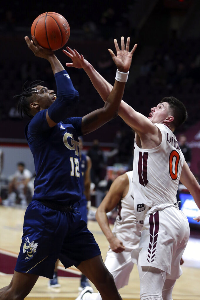Georgia Tech's Khalid Moore (12) shoots over Virginia Tech's Hunter Cattoor (0) during the second half of an NCAA college basketball game Tuesday, Feb. 23, 2021, in Blacksburg, Va. (Matt Gentry/The Roanoke Times via AP, Pool)