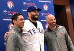Newly signed Texas Rangers pitcher, Lance Lynn, center, wears his new team jersey as he poses for photos with general manager Jon Daniels, left, and manager Chris Woodward, right, after a news conference where Lynn was officially introduced in Arlington, Texas, Tuesday, Dec. 18, 2018. (AP Photo/Stephen Hawkins)