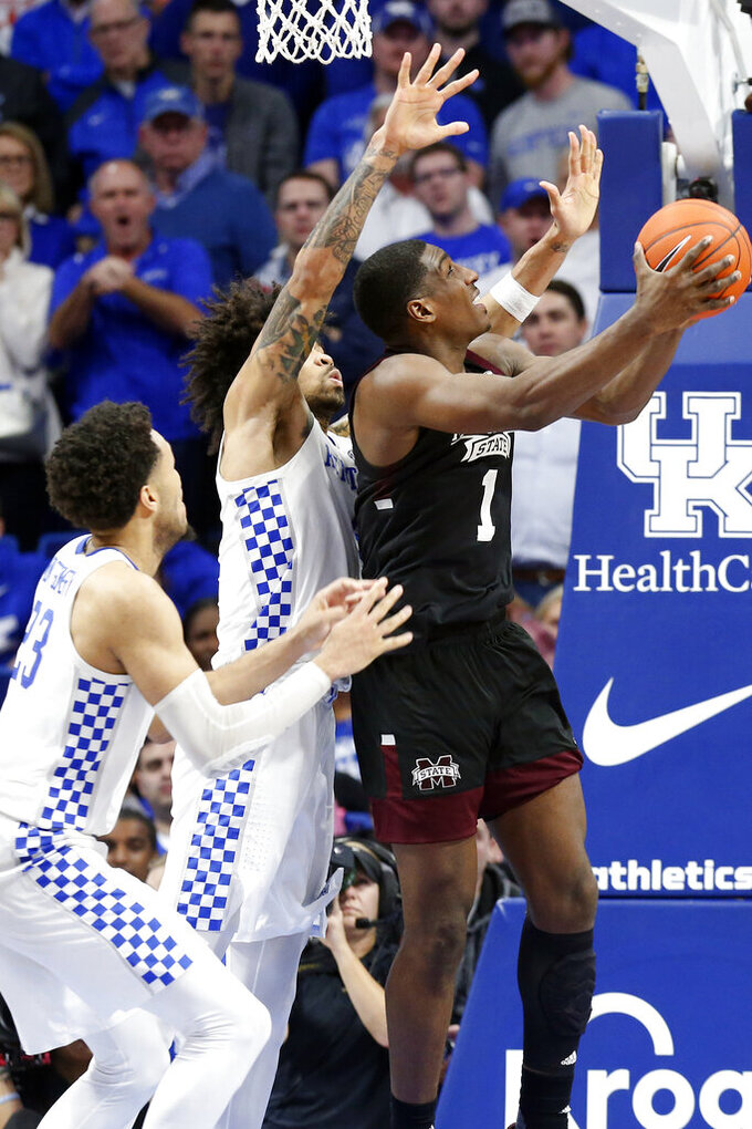 Mississippi State's Reggie Perry, right, shoots while defended by Kentucky's Nick Richards, middle, and EJ Montgomery, left, during the second half of an NCAA college basketball game in Lexington, Ky., Tuesday, Feb. 4, 2020. Kentucky won 80-72. (AP Photo/James Crisp)