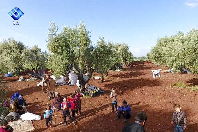 Esta imagen tomada de un video proporcionado por la agencia de noticias Thiqa, muestra a unos residentes que son desplazados de su aldea en el norte de Idlib, Siria, el jueves 9 de mayo de 2019. (Agencia de noticias Thiqa vía AP)