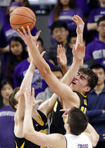 Iowa forward Luka Garza, right, battles for a rebound against forward Nicholas Baer, left, and Northwestern guard Ryan Greer during the second half of an NCAA college basketball game Wednesday, Jan. 9, 2019, in Evanston, Ill. Iowa won 73-63. (AP Photo/Nam Y. Huh)