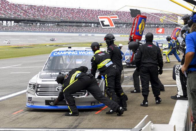Ben Rhodes (99) makes a pit stop during a NASCAR Truck Series auto race Saturday, Oct. 2, 2021, in Talladega, Ala. (AP Photo/John Amis)