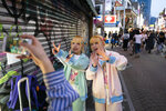 Twins, who go by Kunika and Kuniho, 17, record a greeting for their social media followers in the Harajuku district of Tokyo, June 2, 2019. Harajuku is one of the most popular shopping neighborhoods in Japan. (AP Photo/Jae C. Hong)