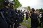Un manifestante sostiene una pancarta mientras salta en repetidas ocasiones para que los policías que se encuentran al fondo puedan verlo el miércoles 27 de mayo de 2020 en la casa del agente Derek Chauvin, quien fue despedido de la policía de Minneapolis, a las afueras de Oakdale, Minnesota. (Jeff Wheeler/Star Tribune vía AP)