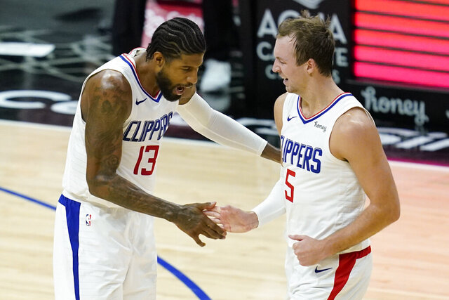 Los Angeles Clippers guards Paul George, left, and Luke Kennard celebrate a point during the third quarter of the team's NBA basketball game against the Minnesota Timberwolves on Tuesday, Dec. 29, 2020, in Los Angeles. (AP Photo/Ashley Landis)