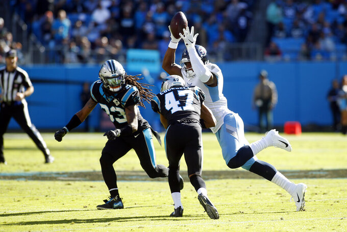 Tennessee Titans tight end Jonnu Smith (81) catches a pass while Carolina Panthers defensive back Tre Boston (33) and defensive back Ross Cockrell (47) defend during the first half of an NFL football game in Charlotte, N.C., Sunday, Nov. 3, 2019. (AP Photo/Brian Blanco)