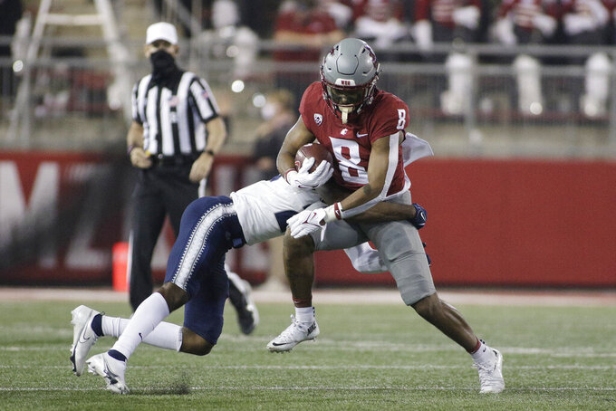 Washington State wide receiver Calvin Jackson Jr., right, tries to get past Utah State safety Dominic Tatum during the first half of an NCAA college football game Saturday, Sept. 4, 2021, in Pullman, Wash. (AP Photo/Young Kwak)
