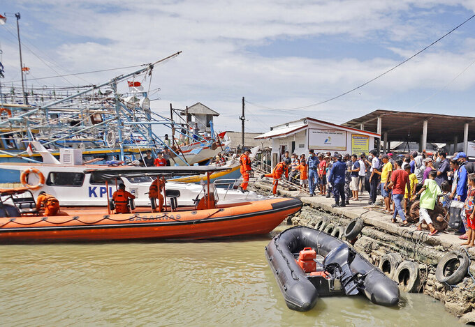 Residents look on as members of National Search and Rescue Agency (BASARNAS) prepare for a search mission for the victims of a ship collision, at a port in Indramayu, West java, Indonesia, Sunday, April 4, 2021. The collision between a cargo ship and a fishing boat left a number of people missing off Indonesia's main island of Java, officials said Sunday. (AP Photo/Panji Wisnu)