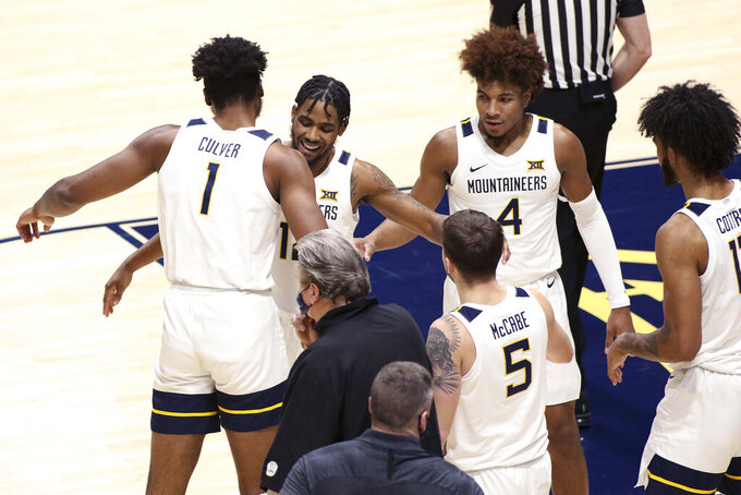 West Virginia forward Derek Culver (1) and guards Taz Sherman (12) and Miles McBride (4) celebrate after Sherman scores during the second half of an NCAA college basketball game against North Texas Friday, Dec. 11, 2020, in Morgantown, W.Va. (AP Photo/Kathleen Batten)