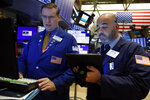 Specialist Patrick King, left, and trader Fred DeMarco work on the floor of the New York Stock Exchange, Monday, Oct. 7, 2019. Stocks are opening broadly lower on Wall Street, extending the market's losing streak into a fourth week. (AP Photo/Richard Drew)