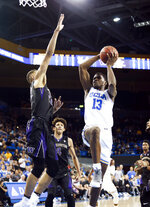 UCLA guard Kris Wilkes, right, goes to the basket against Washington forward Dominic Green during the second half of an NCAA college basketball game in Los Angeles, Sunday, Dec. 31, 2017. UCLA won 74-53. (AP Photo/Ringo H.W. Chiu)