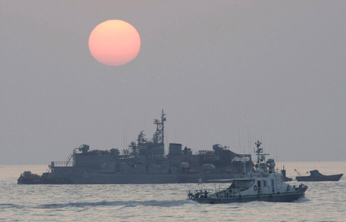FILE - In this Dec. 22, 2010, file photo, a government ship sails past the South Korean Navy's floating base as the sun rises near Yeonpyeong island, South Korea. A South Korean official who disappeared off a government ship near the disputed sea boundary with North Korea this week may be in North Korea, South Korea's Defense Ministry said Wednesday, Sept. 23, 2020. (AP Photo/Ahn Young-joon, File)