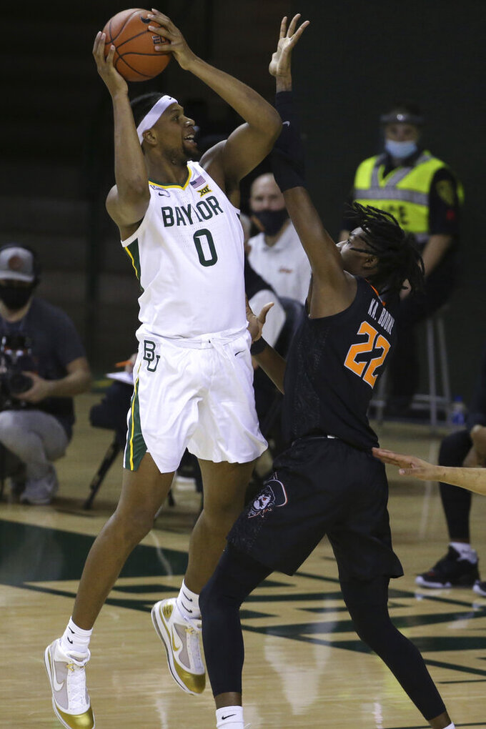 Baylor forward Flo Thamba (0) attempts a shot against Oklahoma State forward Kalib Boone (22) in the first half of an NCAA college basketball game, Thursday, March 4, 2021, in Waco, Texas. (AP Photo/Jerry Larson)