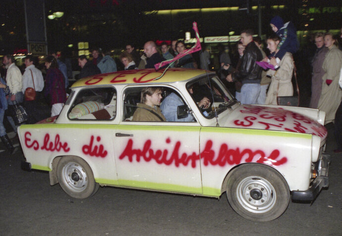 FILE - In this Nov. 11, 1989, file photo a Trabant car, made in East Germany, with a graffiti slogan 'Es lebe die Arbeiterklasse' (Shall the laboring classes live on) is pictured driving in West Berlin, Germany, two days after the boarder between the two Germanys was abolished. The abrupt fall of the Wall in 1989 and lightning speed that reunification took place took everyone by surprise at the time and was a shock to the system for some 16 million East Germans. Unrealistic expectations combined with other factors have helped lead to today's discontent, providing fertile ground for the far-right. (AP Photo/File)