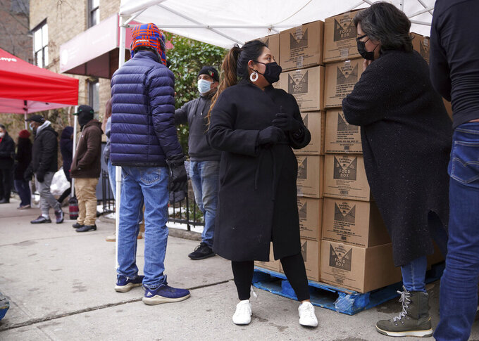 Volunteer Gloria Martinez, left, speaks with Sofia Moncayo, who runs a food distribution program through Mosaic West Queens Church in the Sunnyside neighborhood of the Queens borough of New York on Monday, Feb. 22, 2021. Martinez began volunteering for the program after losing one of her two jobs due to the coronavirus pandemic. (AP Photo/Emily Leshner)
