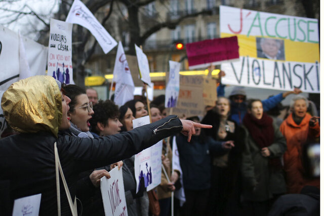 Women demonstrate outside the venue of the Cesar awards ceremony, the French equivalent of the Oscar, Friday,Feb. 28, 2020 in Paris. French women's rights activists protest against multiple nominations for Roman Polanski at the Cesar Awards ceremony. Poster at right reads