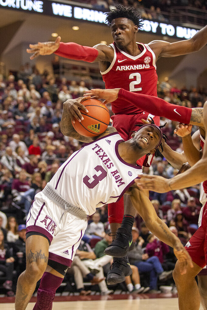 Texas A&M's Quenton Jackson (3) drives to the basket under pressure from Arkansas' Adrio Bailey (2) and Desi Sills during an NCAA college basketball game game at Reed Arena in College Station, Texas, Saturday, March 7, 2020. (Michael Miller/College Station Eagle via AP)