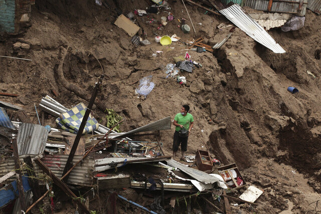 A man seeks to salvage some of his belongings from what used to be his home, destroyed by the waters of the Acelhuate River, in the New Israel Community of San Salvador, El Salvador, Sunday, May 31, 2020. According to the Ministry of the Interior at least seven people died across the country after two days of heavy rains. (AP Photo/Salvador Melendez)