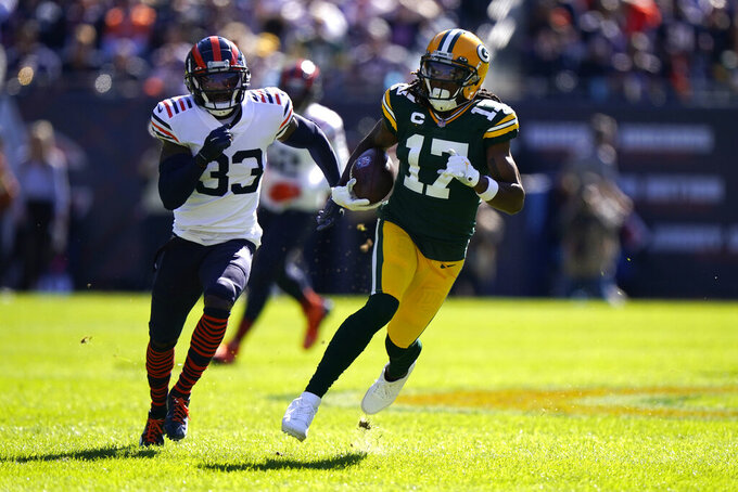 Green Bay Packers wide receiver Davante Adams (17) heads down field on a huge gain off a pass from quarterback Aaron Rodgers as Chicago Bears cornerback Jaylon Johnson pursues during the first half of an NFL football game against the Chicago Bears Sunday, Oct. 17, 2021, in Chicago. (AP Photo/Nam Y. Huh)