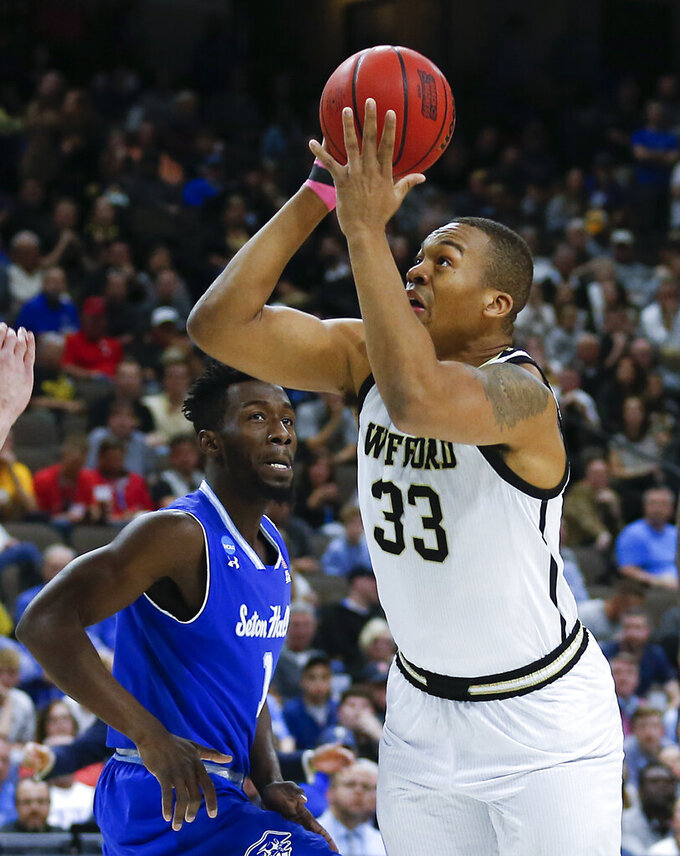Wofford's Cameron Jackson (33) goes up for a shot past Seton Hall's Michael Nzei, left, during the first half of a first-round game in the NCAA men's college basketball tournament in Jacksonville, Fla., Thursday, March 21, 2019. (AP Photo/Stephen B. Morton)