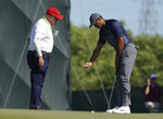 Tiger Woods, right, talks with an official on the tenth green after the wind moved his ball after he addressed it during the first round of the U.S. Open Golf Championship, Thursday, June 14, 2018, in Southampton, N.Y. (AP Photo/Carolyn Kaster)