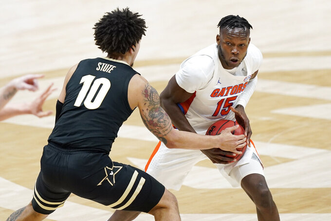 Florida's Osayi Osifo (15) looks for a way around Vanderbilt's Myles Stute (10) in the first half of an NCAA college basketball game in the Southeastern Conference Tournament Thursday, March 11, 2021, in Nashville, Tenn. (AP Photo/Mark Humphrey)