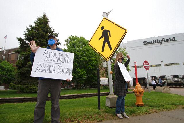 Sioux Falls residents cheered and held thank you signs to greet employees of a Smithfield pork processing plant as they begin their shift on Wednesday May 20, 2020, in Sioux Falls, S.D. Smithfield called many employees back to work after it closed the plant for more than three weeks because of a coronavirus outbreak that infected over 800 employees. (AP Photo/Stephen Groves)