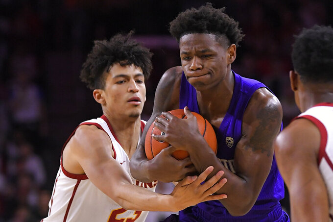 Southern California forward Max Agbonkpolo, left, ties up Washington guard Nahziah Carter during the first half of an NCAA college basketball game Thursday, Feb. 13, 2020, in Los Angeles. (AP Photo/Mark J. Terrill)