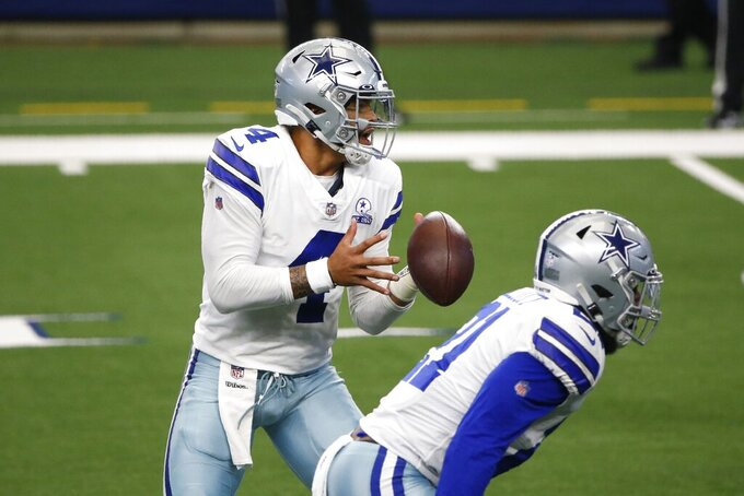 Dallas Cowboys quarterback Dak Prescott bobbles a snap as running back Ezekiel Elliott (21) stands nearby in the first half of an NFL football game against the New York Giants in Arlington, Texas, Sunday, Oct. 11, 2020. (AP Photo/Michael Ainsworth)