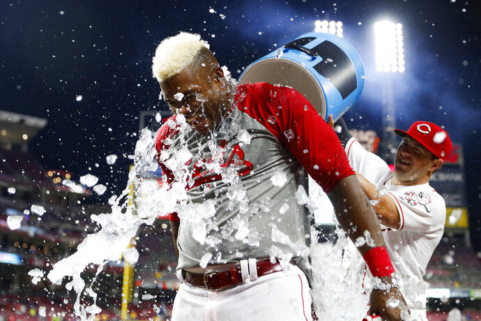 Cincinnati Reds' Yasiel Puig, left, is dunked by Kyle Farmer, right, after hitting the game-winning RBI single off Chicago Cubs relief pitcher Brad Brach in the 10th inning of a baseball game, Wednesday, May 15, 2019, in Cincinnati. (AP Photo/John Minchillo)