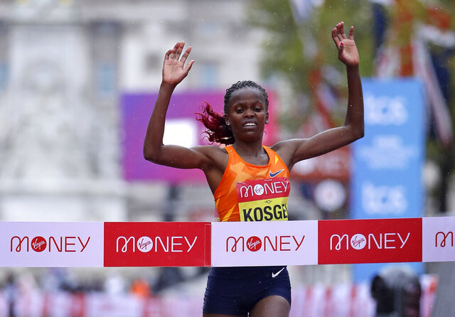 Kenya's Brigid Kosgei crosses the line to win the London Marathon in London, England, Sunday, Oct. 4, 2020. Athletes are competing on a 26.2-mile (42.2-kilometer) closed-loop course consisting of 19.6 clockwise laps around St. James' Park. The traditional course along the River Thames was scrapped because of the coronavirus pandemic and only elite men and women are competing and no spectators are permitted. (Richard Heathcote/Pool via AP)