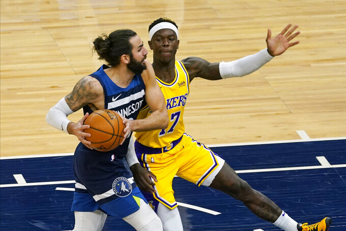 Minnesota Timberwolves' Ricky Rubio, left, drives around Los Angeles Lakers' Dennis Schroder in the first half of an NBA basketball game, Tuesday, Feb. 16, 2021, in Minneapolis. (AP Photo/Jim Mone)