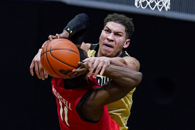 Purdue forward Mason Gillis (0) fouls Maryland guard Darryl Morsell (11) as he shoots during the second half of an NCAA college basketball game in West Lafayette, Ind., Friday, Dec. 25, 2020. (AP Photo/Michael Conroy)