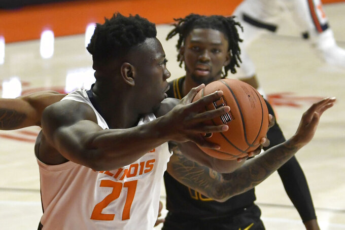 Illinois' Kofi Cockburn (21) protects the ball as North Carolina A&T's Kameron Langley (13) defends during the first half of an NCAA college basketball game Wednesday, Nov. 25, 2020, in Champaign, Ill. (AP Photo/Holly Hart)