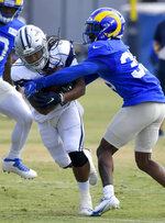 Dallas Cowboys running back JaQuan Hardy is tackled by Los Angeles Rams defensive back Brontae Harris during NFL football practice Saturday, Aug 7, 2021, in Oxnard, Calif. (AP Photo/John McCoy)