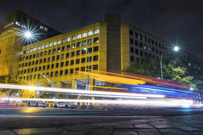FILE - In this Nov. 1, 2017, file photo, traffic along Pennsylvania Avenue in Washington streaks past the Federal Bureau of Investigation headquarters building. Democrats are accusing President Donald Trump of self-dealing as the White House pushes Senate Republicans to include nearly $1.8 billion to rebuild the FBI headquarters in downtown Washington as part of a new coronavirus aid package. Democrats have long accused Trump of a conflict of interest over the FBI building, which sits across the street from a downtown hotel that Trump owns on Pennsylvania Avenue, blocks from the White House. The Trump International Hotel could face competition if the FBI moves from the current site and another hotel is developed on the property. (AP Photo/J. David Ake)