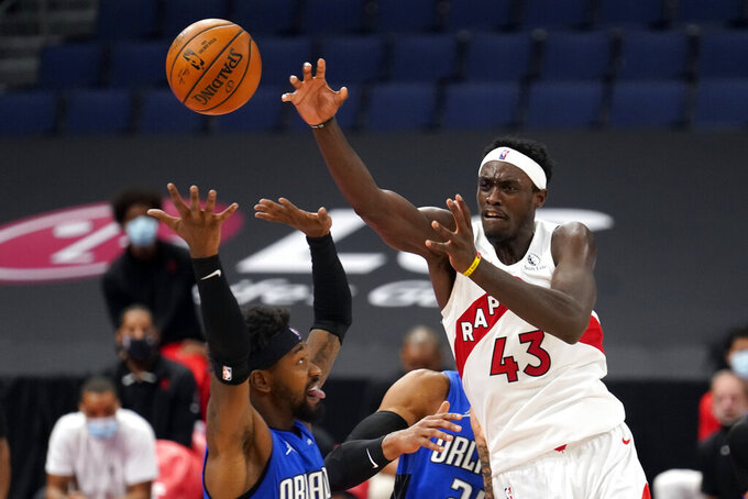 Toronto Raptors forward Pascal Siakam (43) passes the ball over Orlando Magic guard Terrence Ross (31) during the second half of an NBA basketball game Sunday, Jan. 31, 2021, in Tampa, Fla. (AP Photo/Chris O'Meara)