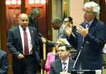 Assembly Speaker Carl Heastie, D-Bronx, left, walks on the Assembly floor as Assemblyman Andy Goodell, R-Jamestown, right, speaks to members of the New York state Assembly against legislation that authorizes state tax officials to release, if requested, individual New York state tax returns to Congress during a vote in the Assembly Chamber at the state Capitol Wednesday, May 22, 2019, in Albany, N.Y. (AP Photo/Hans Pennink)