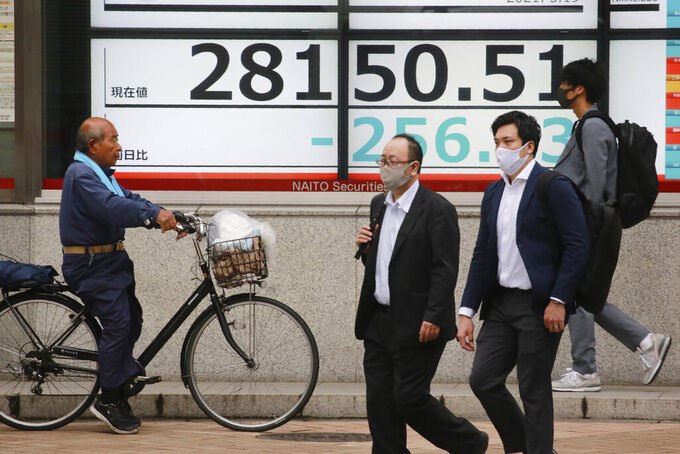 People walk by an electronic stock board of a securities firm in Tokyo, Wednesday, May 19, 2021. Asian shares fell Wednesday, tracking a decline on Wall Street led by big technology stocks. (AP Photo/Koji Sasahara)