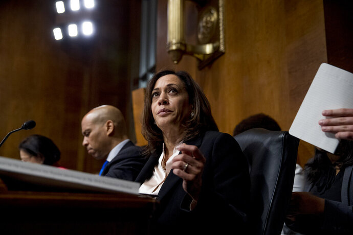 FILE - In a Wednesday, May 1, 2019 file photo, Democratic presidential candidates Sen. Cory Booker, D-N.J., left, and Sen. Kamala Harris, D-Calif., center, listen as Attorney General William Barr testifies during a Senate Judiciary Committee hearing on Capitol Hill in Washington, on the Mueller Report. The Democrats who want to be president are swarming California, competing for campaign cash and media attention while courting longtime allies of home-state Sen. Kamala Harris on their rival's own turf.(AP Photo/Andrew Harnik, File)