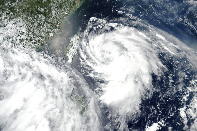 This Sunday, Aug. 2, 2020, satellite image released by NASA shows Typhoon Hagupit approaching Taiwan, center left. Vulnerable coastal areas of eastern China are being evacuated in anticipation of Typhoon Hagupit making landfall late Monday, Aug. 3, 2020, bringing gales and heavy rainfall at a time when much of the country is still recovering from unusually summer heavy flooding.  (NASA Worldview, Earth Observing System Data and Information System (EOSDIS) via AP)