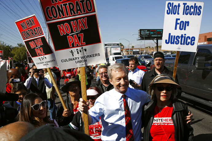 FILE - In this Feb. 19, 2020, file photo, Democratic presidential candidate, businessman Tom Steyer walks on a picket line with members of the Culinary Workers Union Local 226 outside the Palms Casino in Las Vegas. The Democratic presidential contest has moved to immigrant-heavy Nevada, but the issues of immigration are seldom getting a thorough airing on the campaign trail. Candidates usually throw in a quick condemnation of President Donald Trump's hard-line policies but have shied away from outlining their own immigration positions. Immigration groups say that points to a potential vulnerability for whoever is the Democratic nominee later this year. (AP Photo/Patrick Semansky, File)