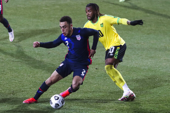 USA's Sergino Dest, left, duels for the ball with Jamaica's Kasey Palmer during the international friendly soccer match between USA and Jamaica at SC Wiener Neustadt stadium in Wiener Neustadt, Austria, Thursday, March 25, 2021. (AP Photo/Ronald Zak)