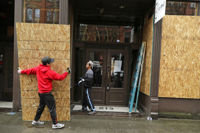 Phu Dang, left, the owner of i5 Pho restaurant, gets help from a contractor as he boards up his business, Monday, March 30, 2020, in Seattle's downtown Pioneer Square neighborhood. Dang closed his business to dine-in customers earlier in the month and had tried doing takeout only food in response to the new coronavirus pandemic, but he said his location did not attract enough customers for take out and he decided to fully close for the time being. He said his decision to board up came after a nearby business was broken into over the weekend. (AP Photo/Ted S. Warren)