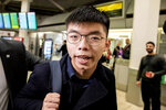 Hong Kong activist Joshua Wong carries a bag as he arrives at the Tegel Airport in Berlin, Germany, Monday, Sept. 9, 2019. Wong will address the media during a press conference in Berlin on Wednesday, Sept. 11, 2019. (Christoph Soeder/dpa via AP)